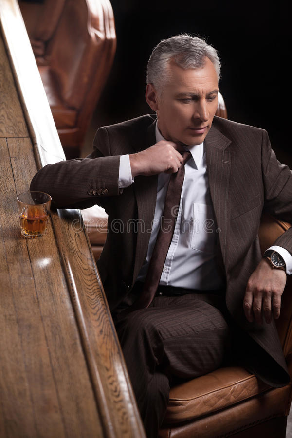 Businessman at the bar. Tired mature businessman sitting at the stock photo
