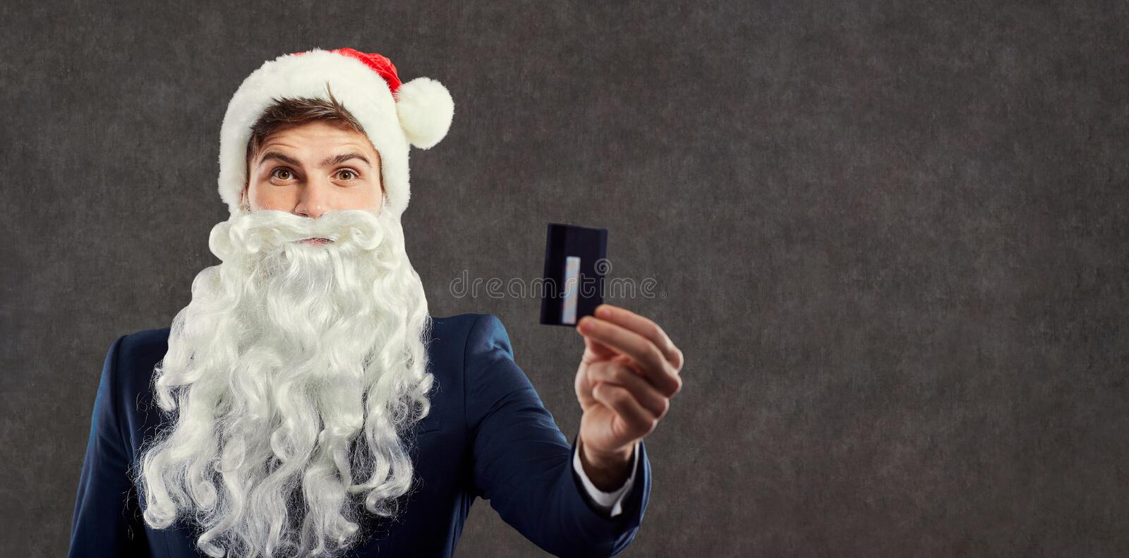 A businessman with a beard in a Santa Claus hat holds a credit c stock photography