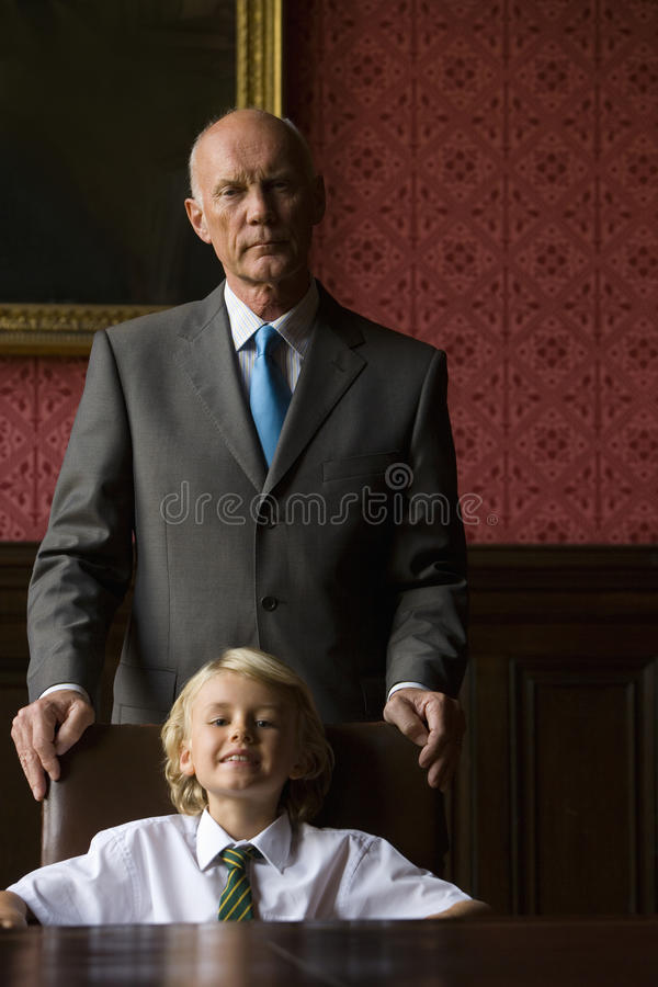 Businessman behind grandson (5-7) in chair at table, smiling, portrait stock photo