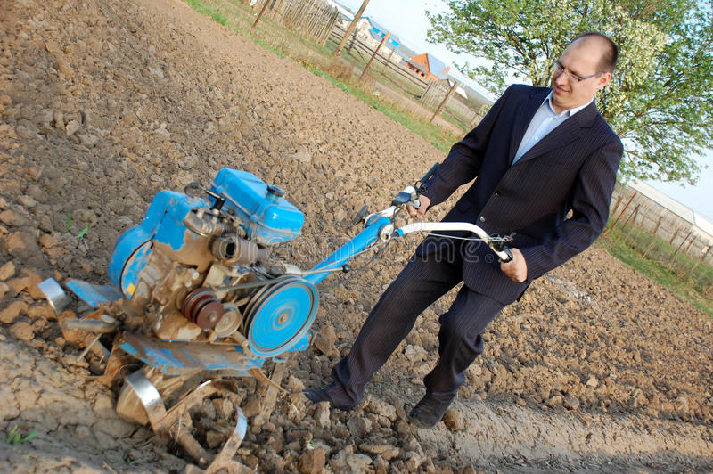 Download The Businessman Behind A Tractor. Stock Image - Image: 14216555