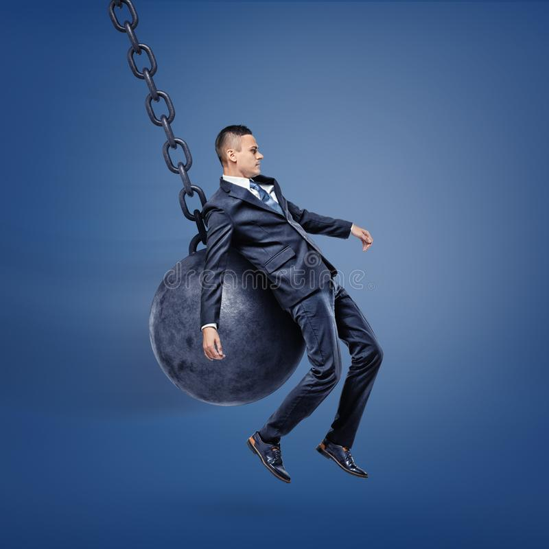 A businessman being hit against his back by a wrecking ball and lifted above the ground. Tough times. Loss of stability. Fly by royalty free stock photos