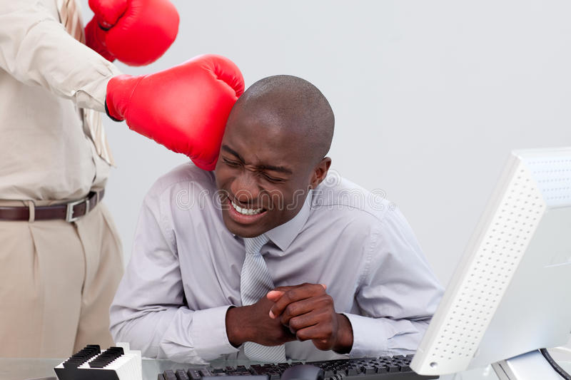 Businessman being hit with a boxing glove stock photos