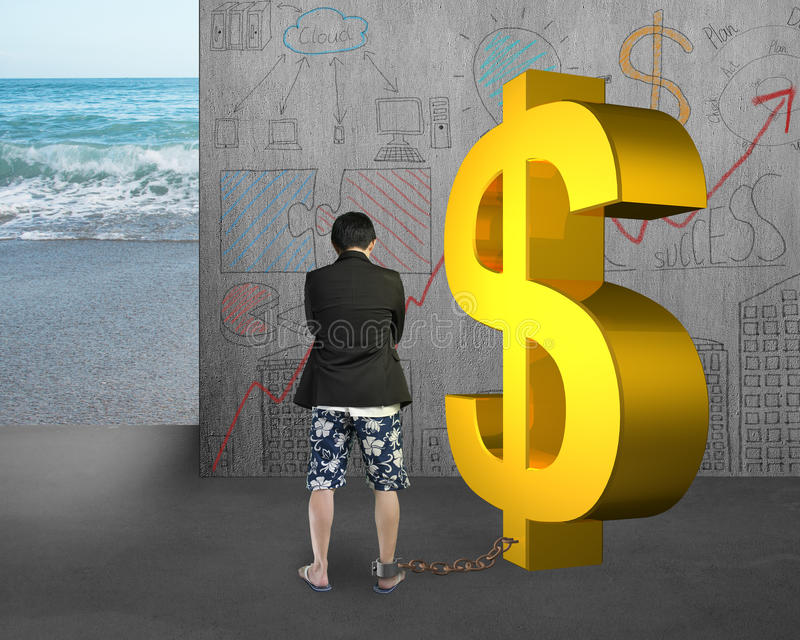 Businessman being shackled with gold dollar. On doodles wall and sea background stock photo