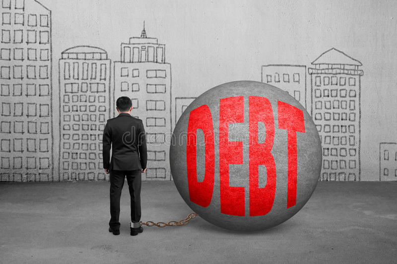 Businessman being trapped with debt ball. And doodles wall royalty free stock image