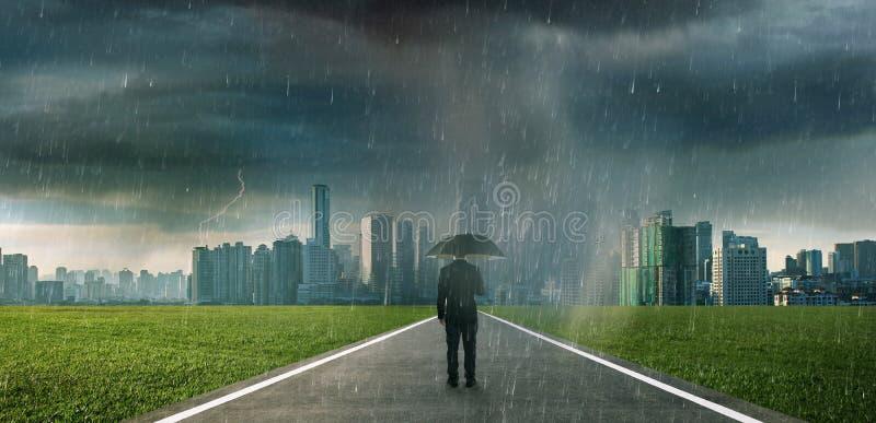 Businessman below storm rain with umbrella stock image