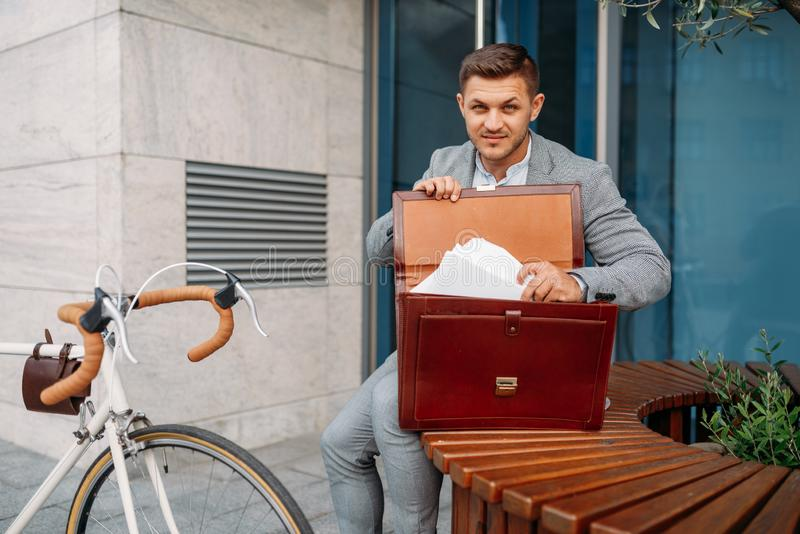 Businessman bicyclist puts document into briefcase royalty free stock photos
