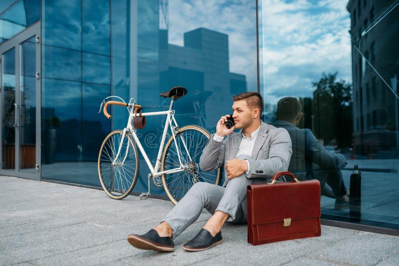 Businessman bicyclist in suit talking by phone stock photos
