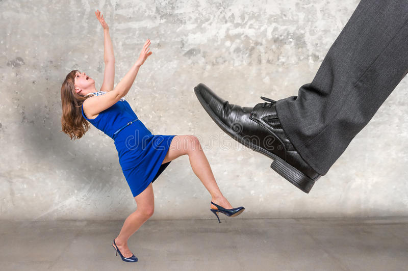 Businessman big foot kicking small businesswoman stock photography