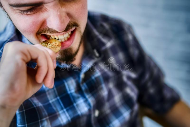 Businessman bites a golden bitcoin for checks authenticity with his teeth royalty free stock images