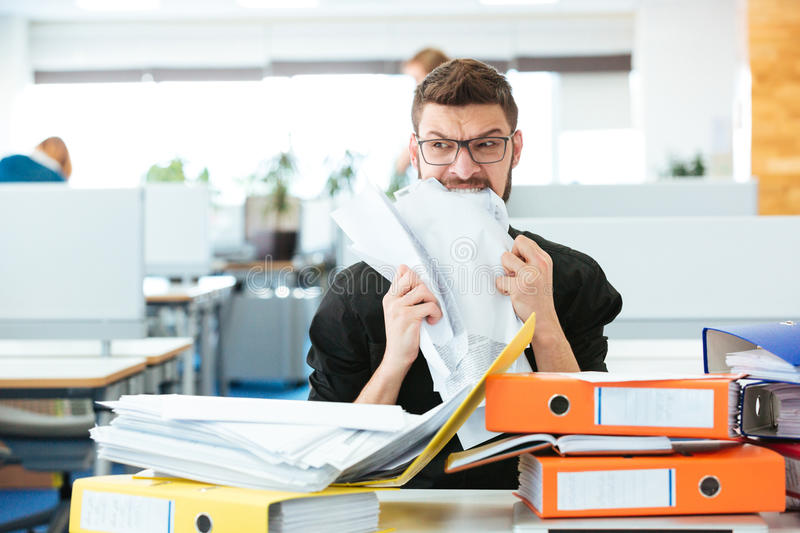 Businessman biting paper in office stock photos