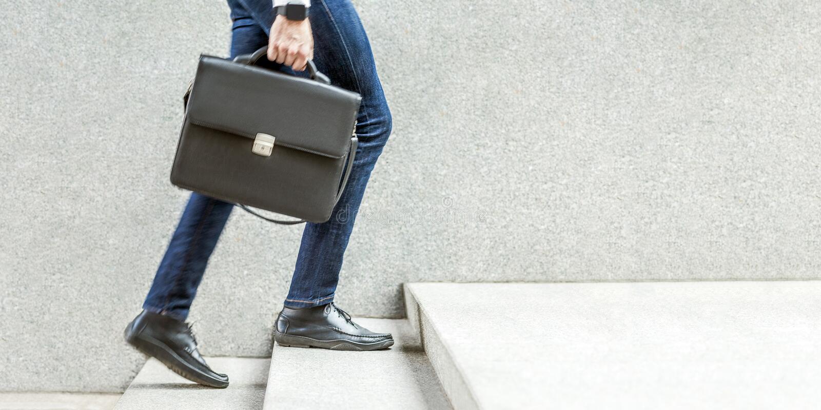 Businessman with black briefcase in hand walking up on stairs. Business goal, improvement, progress, Increase and growth concept. Outdoor closeup shot. in grey royalty free stock photo