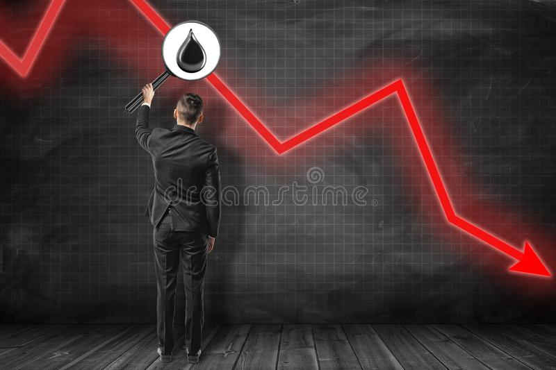 Businessman with black oil drop seen through hand held reading magnifier and red arrow going down on black background stock photo