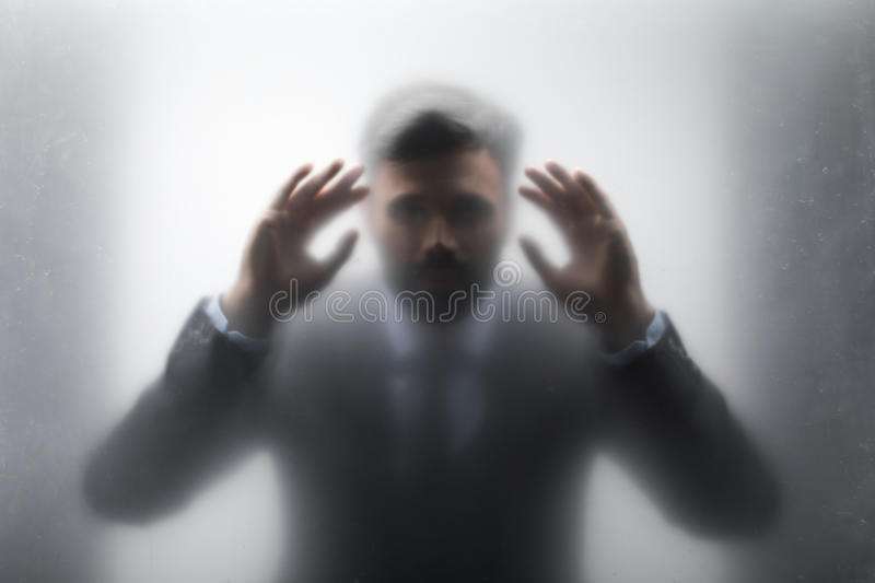 Businessman in black suit looking through the glass stock photography