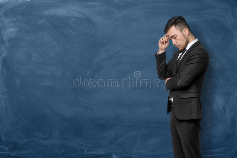 Businessman in black suit standing with his hand on forehead stock photo