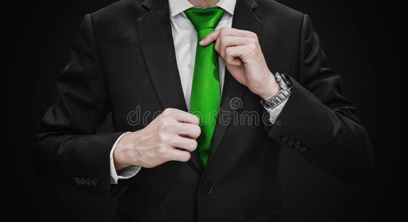 Businessman in black suit tying Green necktie, on black vignette background royalty free stock images