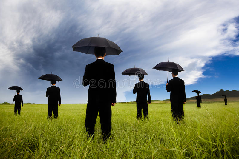 Businessman in black suit watching storm comin. Businessman in black suit holding umbrella and watching the storm coming royalty free stock image
