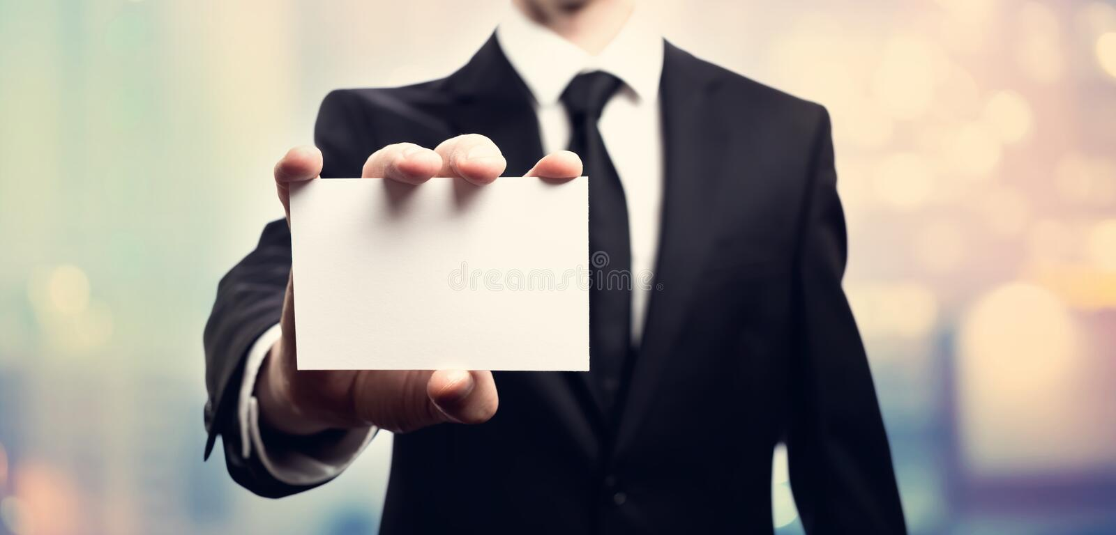 Businessman with a blank business card. On pink and blue abstract light background royalty free stock photography