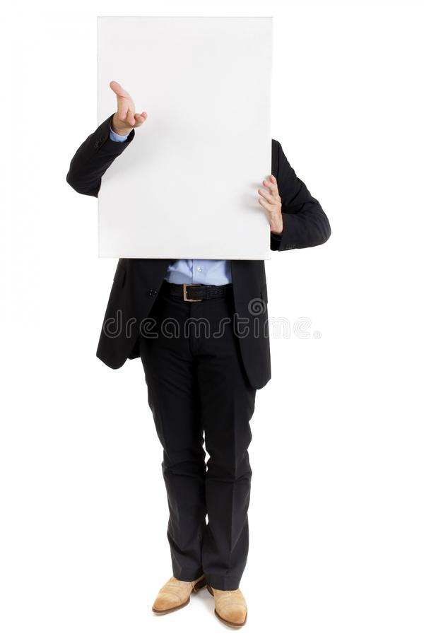 Businessman with a blank sign in front of his face. Businessman in a smart suit standing with a blank white sign held in front of his face gesturing with his royalty free stock photos