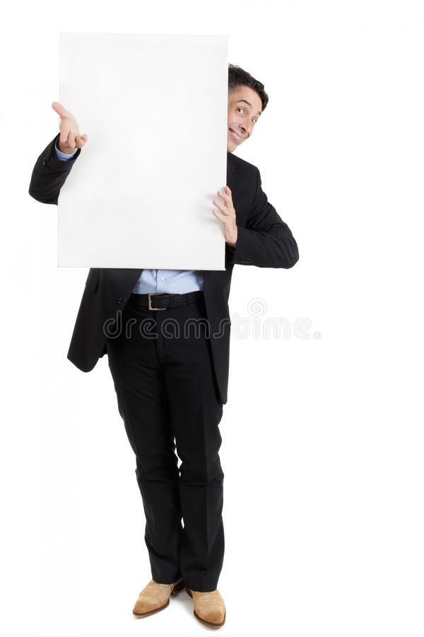 Businessman with a blank white sign. Peering around the side with a smile stock photography