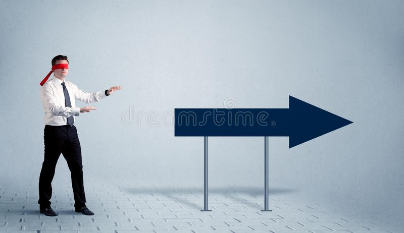 Businessman with blindfolds. A lost young sales person with blindfolds trying to find the right path concept with large blue arrow sign pointing forward stock photo