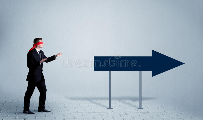 Businessman with blindfolds. A lost young sales person with blindfolds trying to find the right path concept with large blue arrow sign pointing forward stock photography