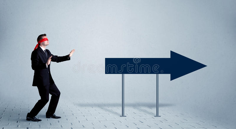 Businessman with blindfolds. A lost young sales person with blindfolds trying to find the right path concept with large blue arrow sign pointing forward royalty free stock image