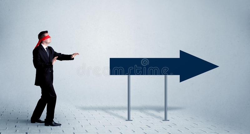 Businessman with blindfolds. A lost young sales person with blindfolds trying to find the right path concept with large blue arrow sign pointing forward stock images