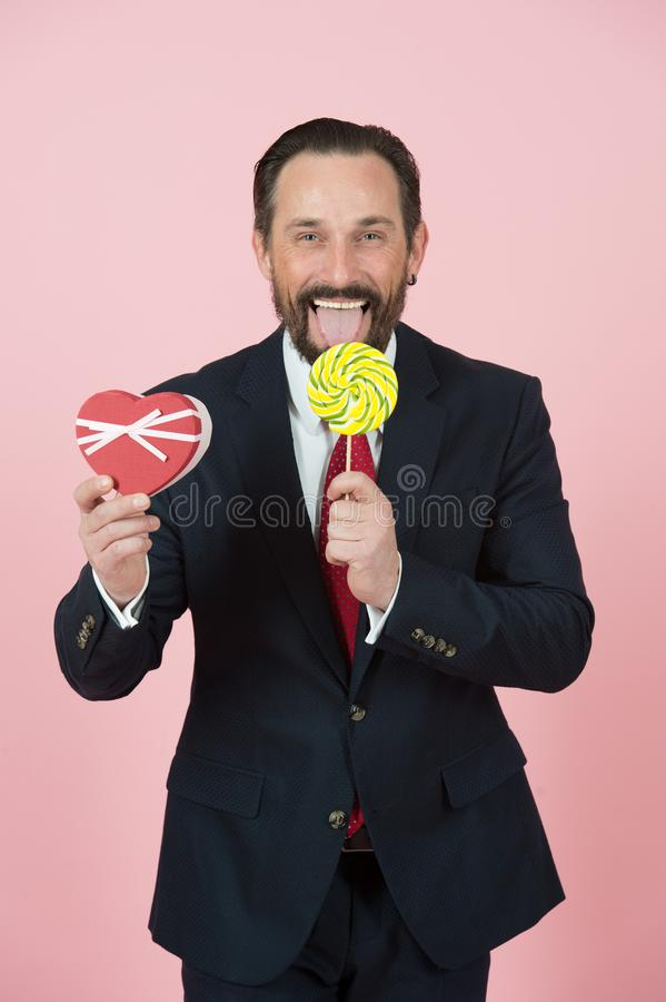Businessman in black suit licking lollipop. Manager face emotion with red box in studio. Man makes present and loves candy. Businessman in blue suit licking royalty free stock photo