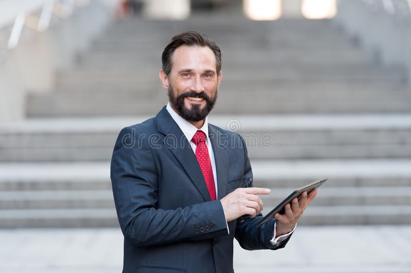 Businessman in blue suit and red tie working on digital tablet in front of office building stock photo