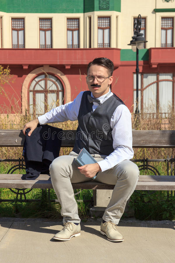 Businessman with a book sitting on the bench stock photo
