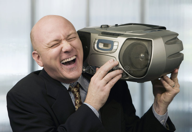 Businessman with Boom Box. Bald businessman listening to a boom box stock image