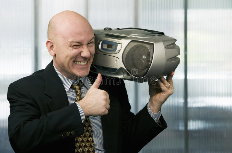 Businessman with Boom Box. Bald businessman listening to a boom box stock photo