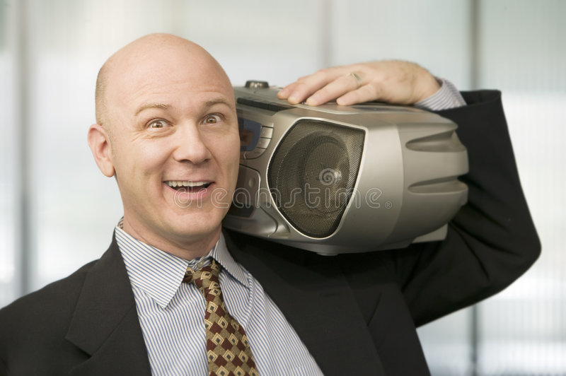 Businessman with a Boom Box. Smiling Businessman listening to a big Boom Box royalty free stock photos