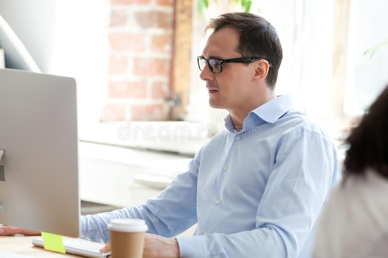 Businessman, boss looking at monitor screen squinting. Serious businessman, boss in glasses looking at monitor screen squinting, working with document, writing stock images