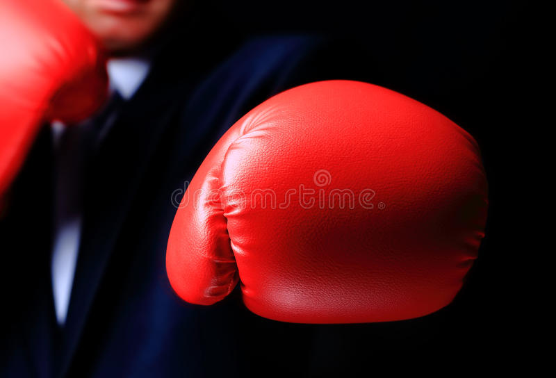 Businessman in boxing gloves. On black stock photos