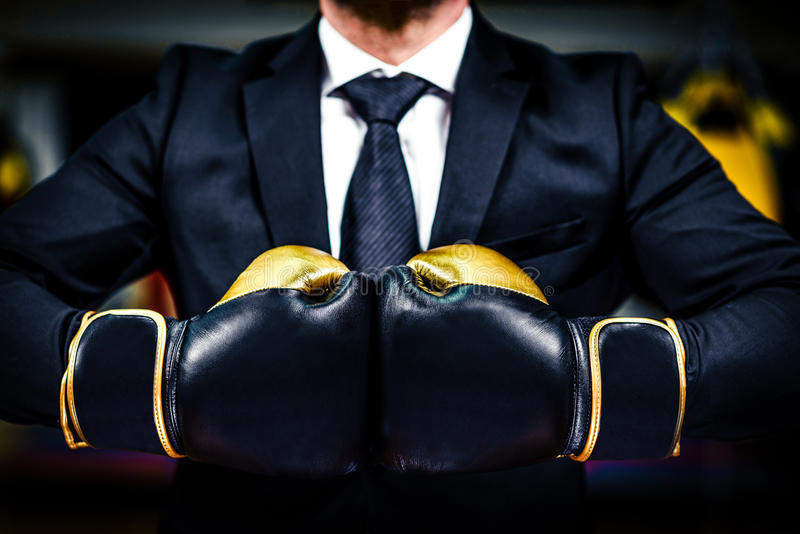 Businessman with boxing gloves is ready for corporate battle. Man in suit, shirt and a tie is holding combat gloves together. Shot in a boxing gym, concept of royalty free stock images