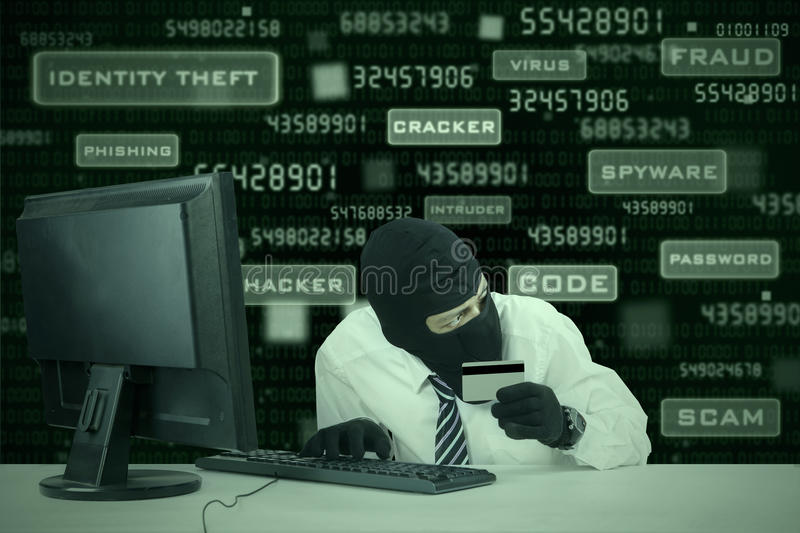 Businessman breaking credit card security 1. Internet Theft - businessman wearing a mask and holding a credit card while sat behind a computer stock images