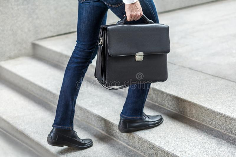 Businessman with briefcase in hand walking up on stairs. royalty free stock photos