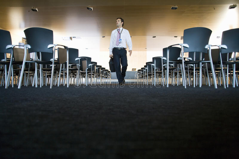 Businessman with briefcase leaving empty lecture hall royalty free stock photo