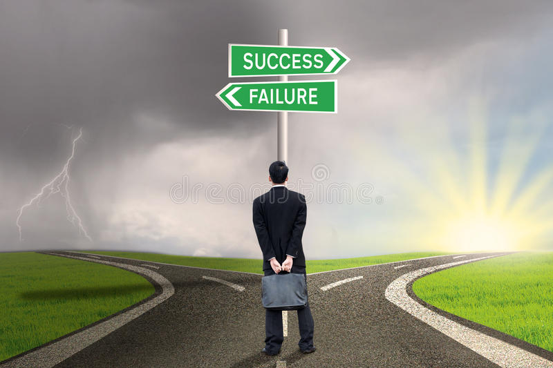 Businessman with briefcase looking at success or failure. Businessman is holding briefcase and standing on the road with a sign of success or failure royalty free stock image