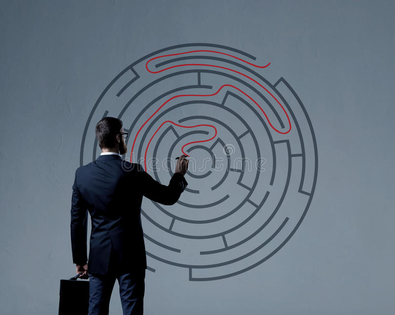 Businessman with briefcase standing over labyrinth background. B royalty free stock images