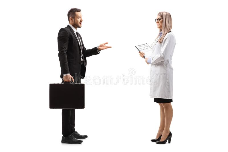 Businessman with a briefcase talking to a young female doctor royalty free stock image
