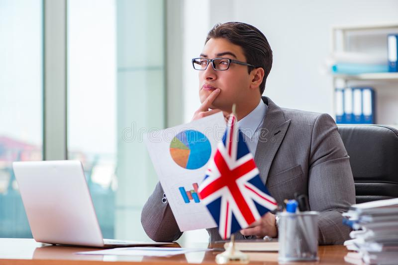 The businessman with british flag in the office. Businessman with British flag in the office stock photos