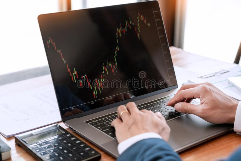 Businessman or broker looking at computer laptop analysing about stock market invest trading stocks graph analysis candle line in royalty free stock photography