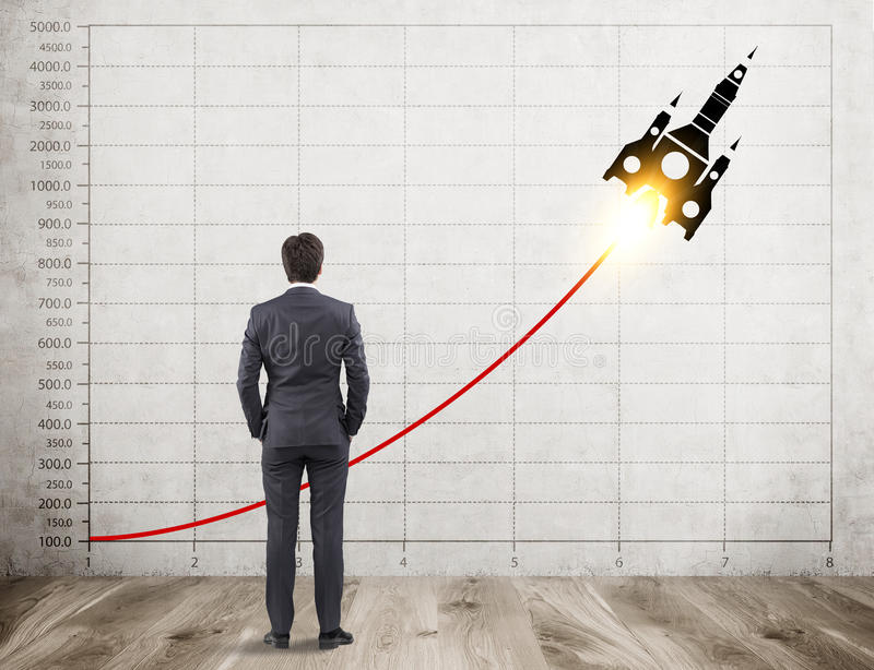 Businessman with brown hair is looking at rocket sketch and graph. Rear view of businessman with brown hair looking at concrete wall with graph and a rocket royalty free stock image