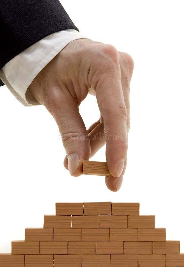 Businessman building a bricks wall stock images