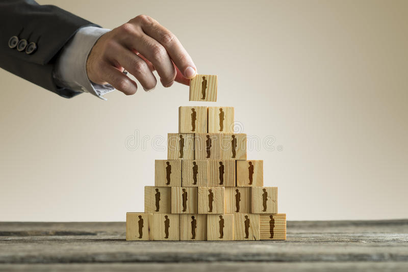 Businessman building a pyramid of wood blocks with people silhouettes royalty free stock image
