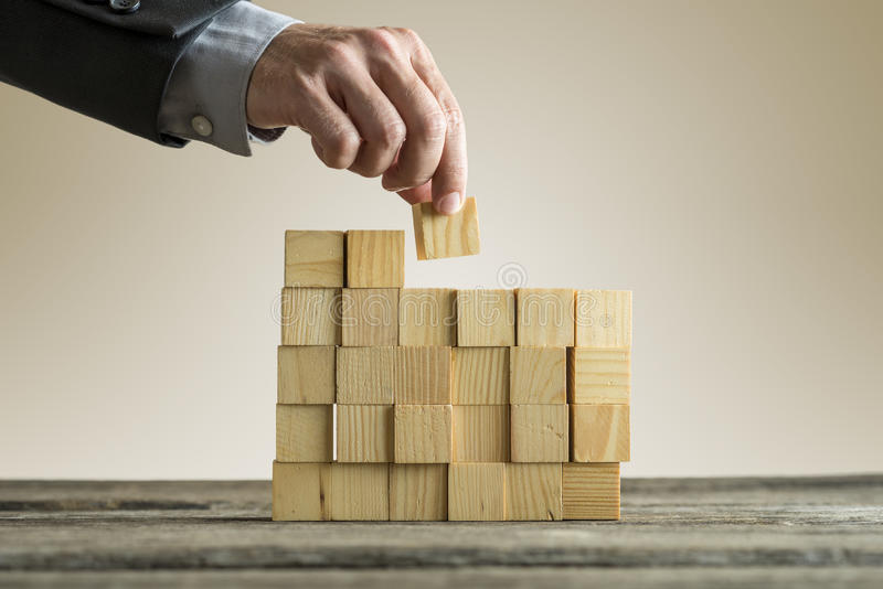 Businessman building a structure with wooden cubes on table surf stock photo