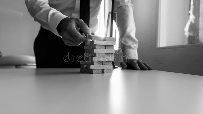 Businessman building a tower of stacked blocks of wood stock photo