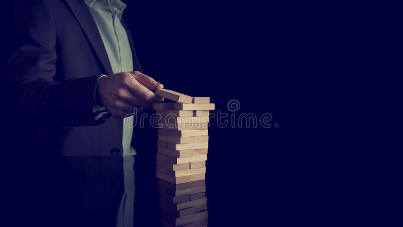 Businessman building a tower of stacked blocks stock photography